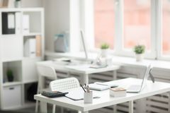 Supplies on workplace. Group of office supplies on desk with chair near by on background of another workplace by window Stock Photo