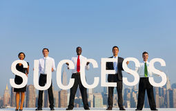 A Group Of Office Workers Holding SUCESS Letters Stock Photo