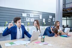 A group of office workers spend working time and one asleep. Stock Images
