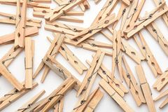 A group of old fashioned wooden clothes pins on a white surface. A large group of old fashioned wooden clothes pins on a white surface royalty free stock photography