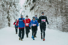 Group older male athletes running snow-covered alley in Park Stock Image