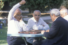 A group of older men playing backgammon Royalty Free Stock Image