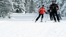 Group of older people enjoy skiing in winter