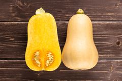 Smooth pear shaped orange butternut squash waltham on brown wood. Group of one whole one half of smooth pear shaped orange butternut squash waltham variety stock photography