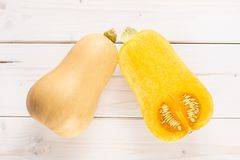 Smooth pear shaped orange butternut squash waltham on grey wood. Group of one whole one half of smooth pear shaped orange butternut squash waltham variety royalty free stock image