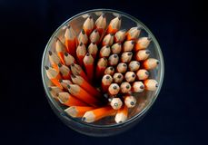 Group of orange pencil inside circular container, black background Royalty Free Stock Images