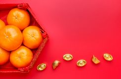 Group of orange tangerine in Chinese pattern tray with gold ingo. Ts on red table top. Chinese new year concep.Chinese Language ingot is wealthy Royalty Free Stock Photos
