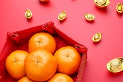 Group of orange tangerine in Chinese pattern tray with gold ingo. Ts on red table top. Chinese new year concep.Chinese Language ingot is wealthy Royalty Free Stock Photo