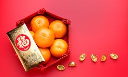 Group of orange tangerine in Chinese pattern tray and golden envelope packet ang pow with gold ingots on red table top. Chinese n. Ew year concept.leave space royalty free stock photos