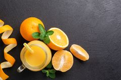 A group of oranges and a glass of juice on a dark background. stock images