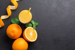 A group of oranges and a glass of juice on a dark background stock photography