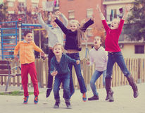 Group of ordinary kids in high spirits jumping. Outdoors Stock Photos