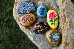 Group of painted rocks on a small boulder. A group of six painted rocks are on a small boulder. Colorful rocks have various pictures and words such as `Pray,` ` stock illustration