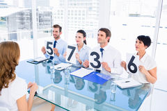 Group of panel judges holding score signs in front of woman Royalty Free Stock Photography