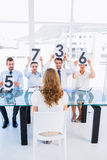 Group of panel judges holding score signs in front of woman Royalty Free Stock Photo