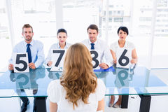 Group of panel judges holding score signs in front of woman Stock Image
