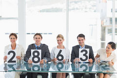 Group of panel judges holding score signs Royalty Free Stock Image