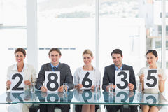 Group of panel judges holding score signs Stock Image