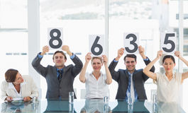 Group of panel judges holding score signs Stock Photos