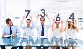 Group of panel judges holding score signs Royalty Free Stock Photos