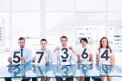 Group of panel judges holding score signs Stock Photography