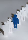Group of paper-men standing in a row royalty free stock photo