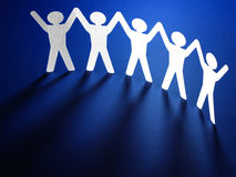 Group of paper people holding hands. Stock Images