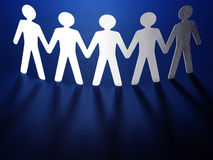Group of paper people holding hands. Stock Image