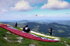 Group of paragliding students during an instruction course and flying lesson in the Alps. A group of paragliding students during an instruction course and flying Royalty Free Stock Image