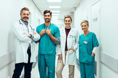 Group of paramedics standing in hospital corridor. Portrait of positive medical professionals standing in hallway and looking at camera. Group of paramedics stock photos