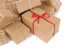 Isolated pile of brown paper packages, one unique with red ribbon Stock Image