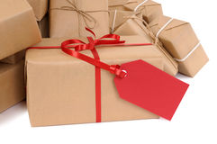 Several brown paper packages, red gift tag, copy space, isolated on white Stock Images
