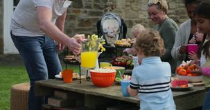 Serving the Refreshments. Group of parents and children sitting outdoors and enjoying a easter garden party. They are enjoying food and drink