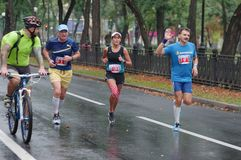 Group of participants following cyclist during 42 km distance of ATB Dnipro Marathon Stock Photos