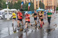 Group of participants at the head of pacemakers running on the central street of Dnipro city Stock Photos