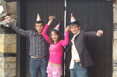 Group of party friends. Group of friends wearing party hats posing over a old black door stock images