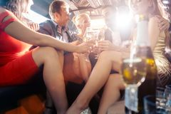 Group of party people in a limo drinking. Looking at the camera royalty free stock image