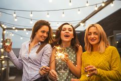 Group of partying girls with flutes with sparkling wine and bengal fire. Having fun on the party royalty free stock photo