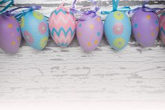 A group of pastel colored Easter eggs on a white wooden background stock photo