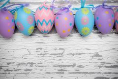 A group of pastel colored Easter eggs on a white wooden background stock photography
