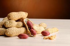 Group of peanuts on the table and brown background. Group of peanuts on the white table and brown background Stock Photos