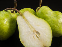Group of pears and half pear. On black Royalty Free Stock Photo