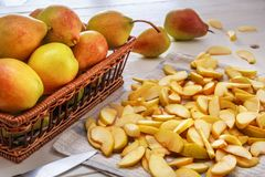 Group of pears and sliced pears on white wooden boards with a textile napkin stock image
