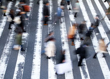 Group of pedestrians crossing the street. At a zebra crossing with motion blur to the people and focus to the markings on the road, high angle view Stock Images