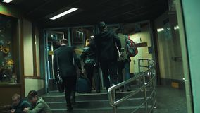 Group of pedestrians walks metro station entrance doors at night. Man with skateboard, fly attendant with bag, tramps on stairs stock footage