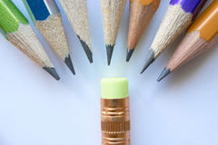 Group of pencils and small eraser. Group of pencils standing in a semicircle humiliating small eraser. concept of a schoolchild in new school or bad pupils bully royalty free stock images