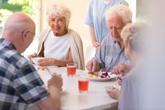 Pensioners eating lunch. Group of pensioners eating lunch together at the rest home royalty free stock photography