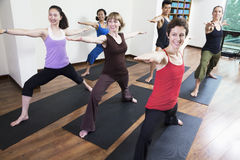 Group of people with arms outstretched doing yoga during a yoga class Stock Image