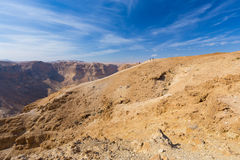 Group of people ascending desert mountain slope. Stock Image