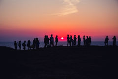 A group of people on the background of sunset. A group of people on the background of beautiful sunset in Crimea Stock Photo